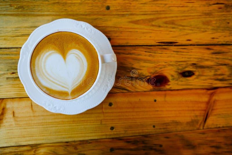 Kawowa latte sztuka na drewnianej filiżance zdjęcia royalty free