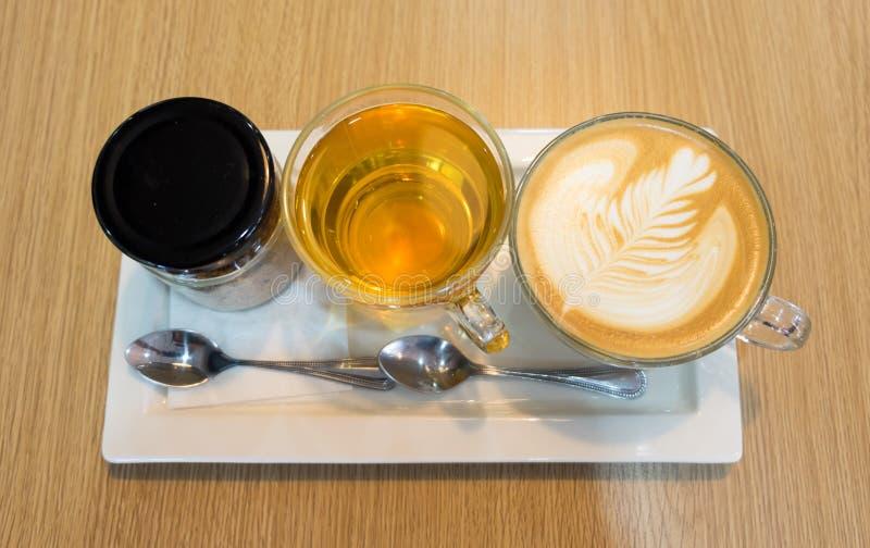 Kawowa opóźniona sztuka w filiżance i cukrowej filiżance na bielu talerzu na drewnianym stole butelki i herbacianej obraz royalty free