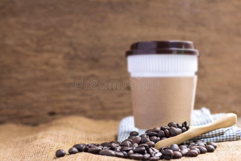 Kawowa plastikowa filiżanka z kartonowym rękawem i stosem kawa był obrazy stock