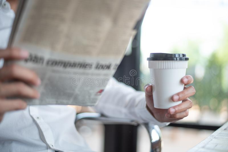 Kawowa przerwa i szukać dla wiadomości informaci, biznesowego mężczyzna chwyt obraz royalty free