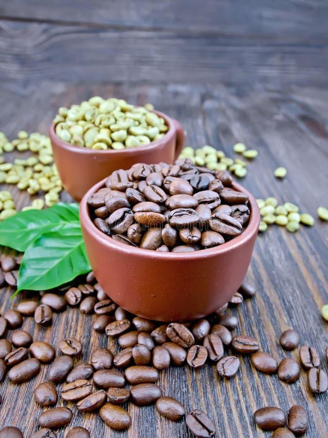 Kawowe czarne i zielone adra w filiżankach z liściem na pokładzie obrazy royalty free