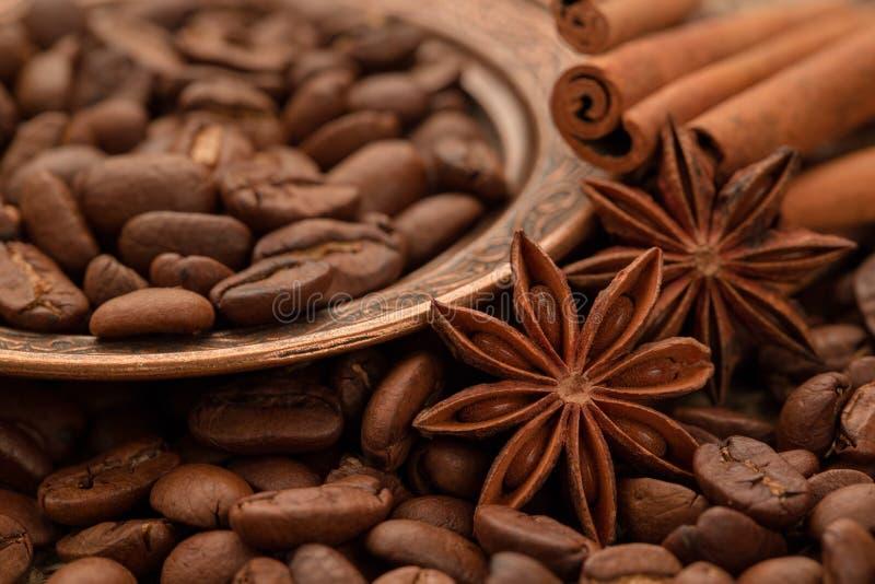 Kawowe fasole, cynamon i anyż na miedzianym talerzu, fotografia royalty free