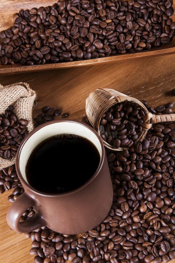 Kawowe fasole, drewniany stół z nastrojowym światłem zdjęcia stock