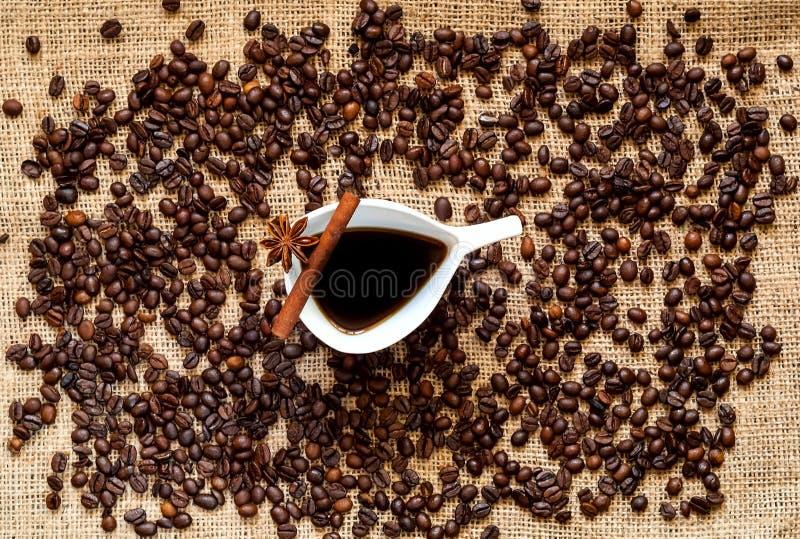 Kawowe fasole i rocznik biała ceramiczna filiżanka kawy, cynamonowi kije, anyż gwiazdy na jutowym worku kosmos kopii z bliska zdjęcia royalty free