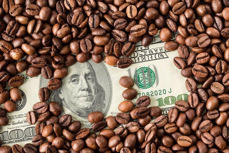 Kawowe fasole i sto dolarowi rachunków zdjęcie stock