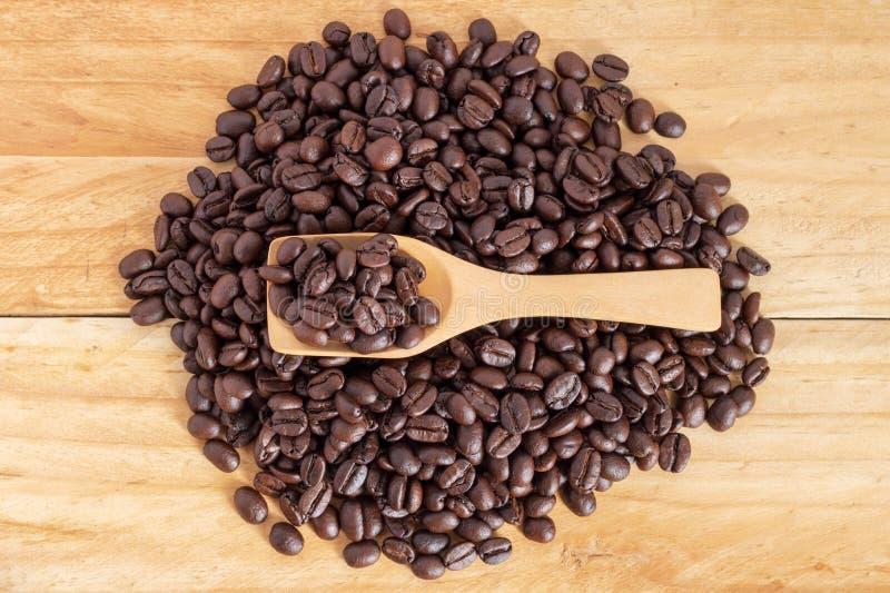 Kawowe fasole i zmielona kawa w łyżce na textured drewnie, widok zdjęcia stock