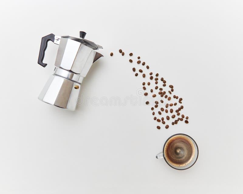 Kawowe fasole nalewają wewnątrz nakrętkę z napojem od metalu kawowego producenta na białym tle Mieszkanie nieatutowy fotografia royalty free