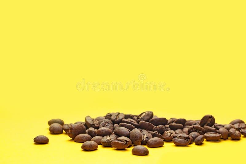Kawowe fasole odizolowywać na żółtym tle Radosny temat fotografia royalty free
