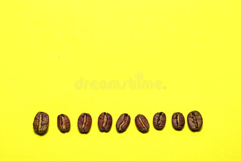 Kawowe fasole odizolowywać na żółtym tle Radosny temat zdjęcie royalty free