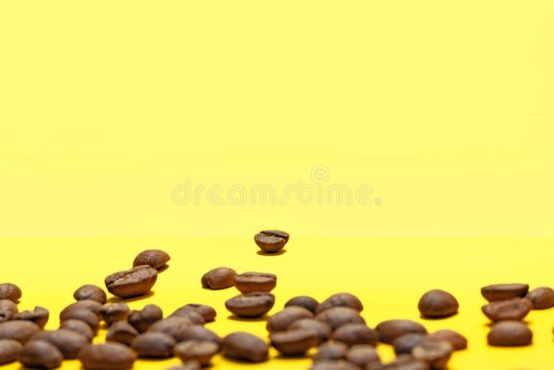 Kawowe fasole odizolowywać na żółtym tle Radosny temat zdjęcia stock