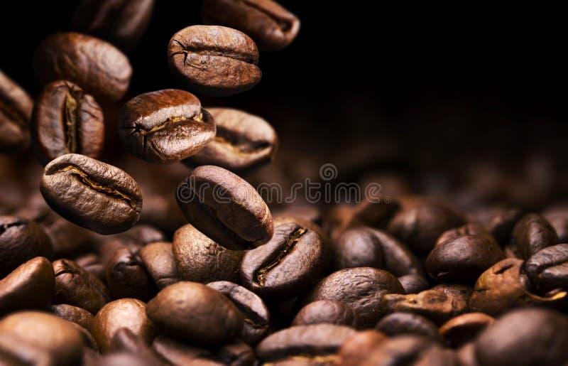 Kawowe fasole spada na stosie, czarny tło z kopii przestrzenią, zakończenie w górę zdjęcie stock