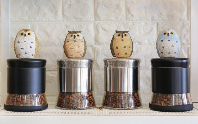 Kawowe fasole w butelce z sowy statuą Nie sen jak sowy pojęcie obraz stock