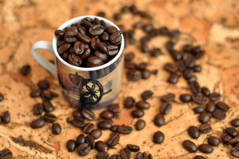Kawowe fasole w filiżance na stole i zdjęcie stock