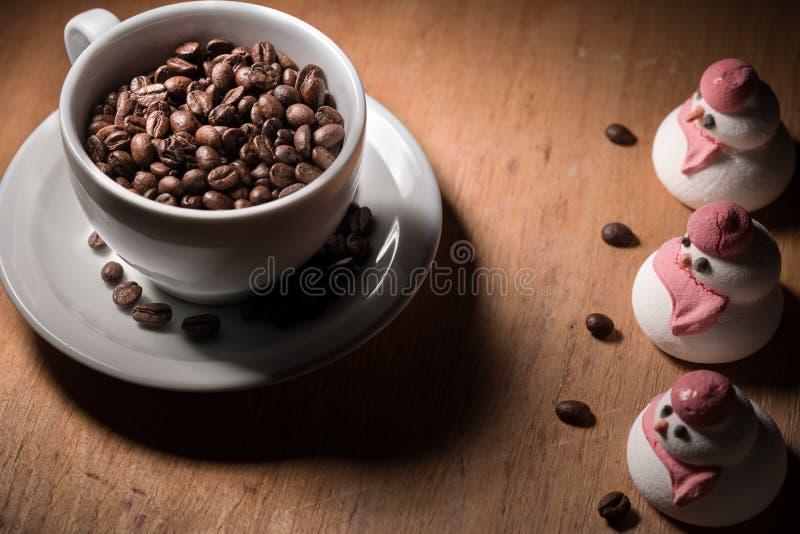 Kawowe fasole w filiżance z niektóre przyjaciółmi zdjęcia stock