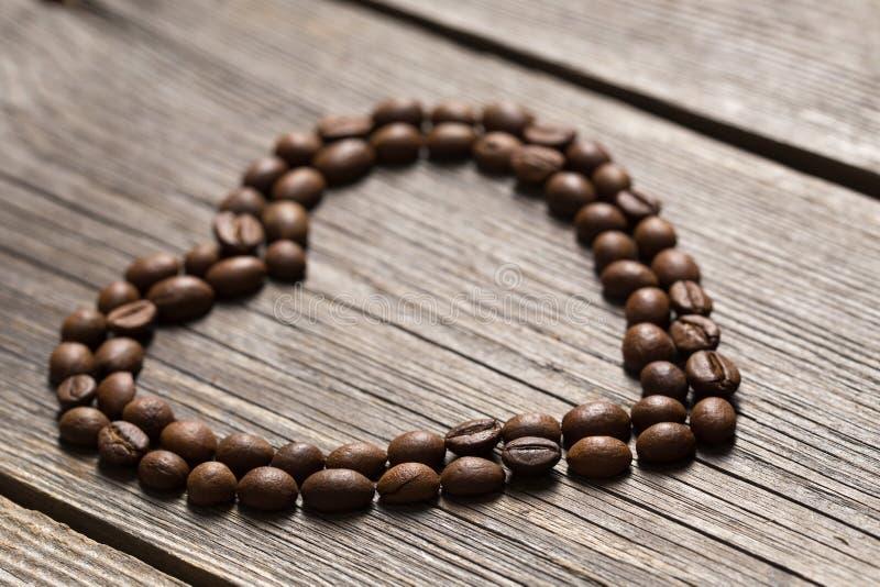 Kawowe fasole w kierowym kształcie na drewnianym tle obraz stock