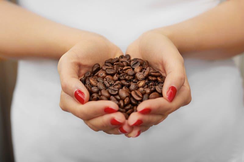 Kawowe fasole w kobiet rękach z czerwonymi gwoździami na białym koszulki tle zdjęcie stock