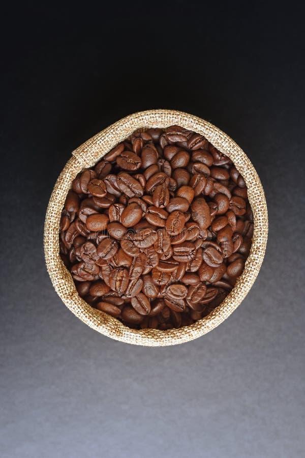 Kawowe fasole w konopie grabiją na czarnym tle obrazy royalty free