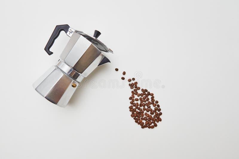 Kawowe fasole w postaci opadowego obcieknięcia od metalu kawowego producenta na białym tle z przestrzenią dla teksta Pojęcie zdjęcie royalty free