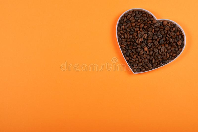 Kawowe fasole w sercowatym talerzu na pomarańczowym tle fotografia stock