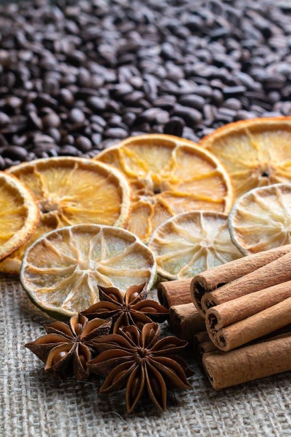 Kawowe fasole z cytrusów cynamonowymi kijami i gwiazdowym anyżem na tle burlap zdjęcia royalty free