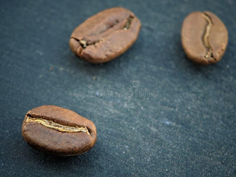 Kawowe fasole zamknięte w górę czarnej tło deski na obraz stock