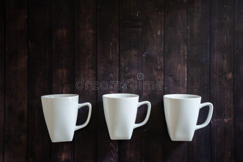 3 kawowego kubka na drewnianym stołowym tle - ranek podnosi ja w górę napoju obrazy stock