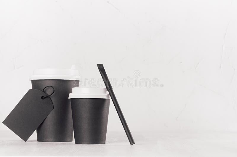 Kawowego mockup - duże, małe czarne papierowe filiżanki z białymi nakrętkami z kopii przestrzenią, pusta etykietka i cukrowa torb obrazy stock
