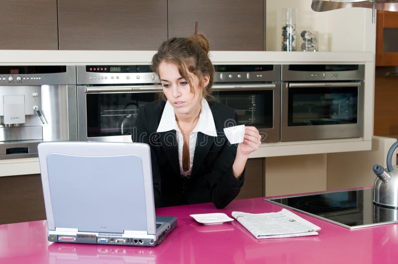 kawowego wykonawczego kuchennego laptopu przyglądająca kobieta zdjęcie stock