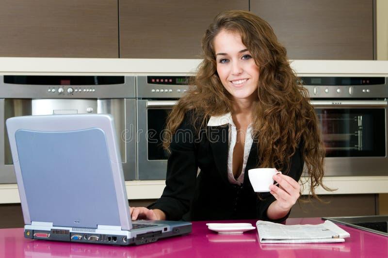 kawowego wykonawczego kuchennego laptopu przyglądająca kobieta zdjęcia royalty free