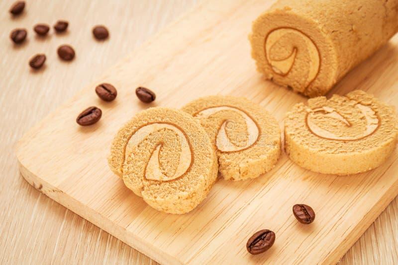 Kawowej rolki tort na drewnianej desce i kawowych fasolach zdjęcia royalty free
