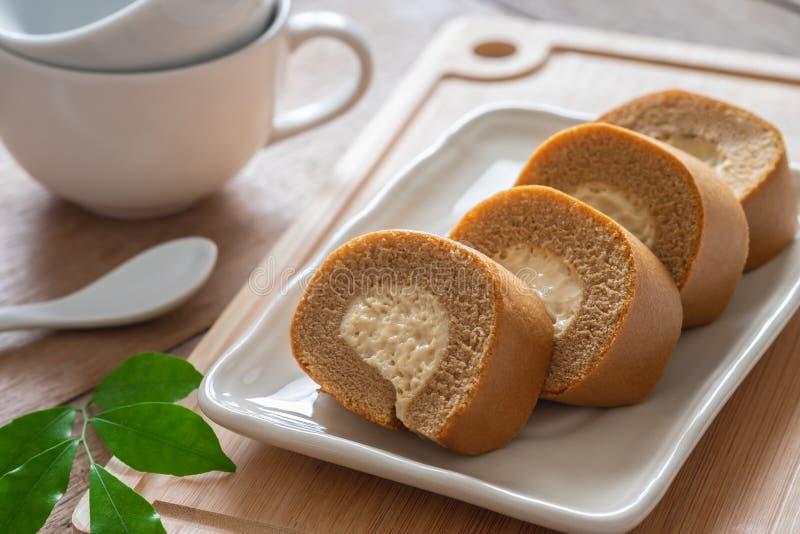 Kawowej rolki tort z śmietanką na talerzu i filiżance fotografia stock