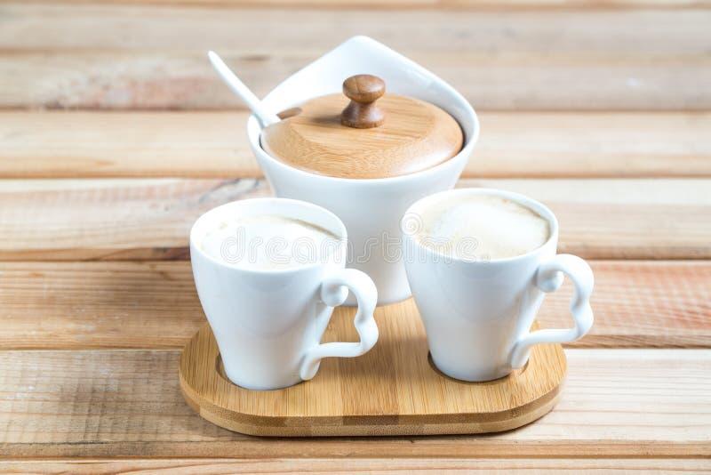 Kawowi creamery Dwa filiżanki kawy na drewnianym stole zdjęcie stock