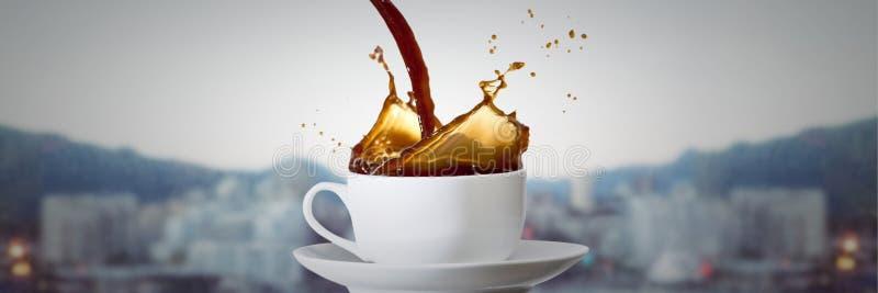 Kawowy dolewanie w białą filiżankę z spodeczkiem przeciw rozmytej linii horyzontu obrazy royalty free