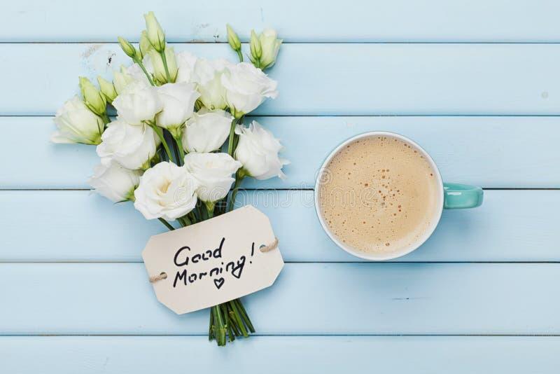 Kawowy kubek z białymi kwiatami i notatka dzień dobry na błękitnym wieśniaka stole od above Piękny śniadaniowy mieszkanie nieatut fotografia royalty free