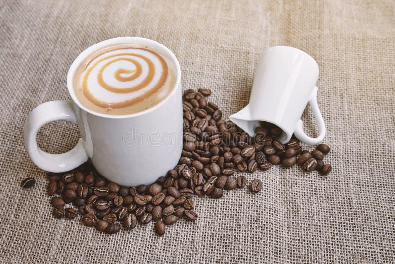 Kawowy latte karmelu macchiato na białej filiżance z kawową fasolą z niektóre tekst przestrzeń fotografia stock