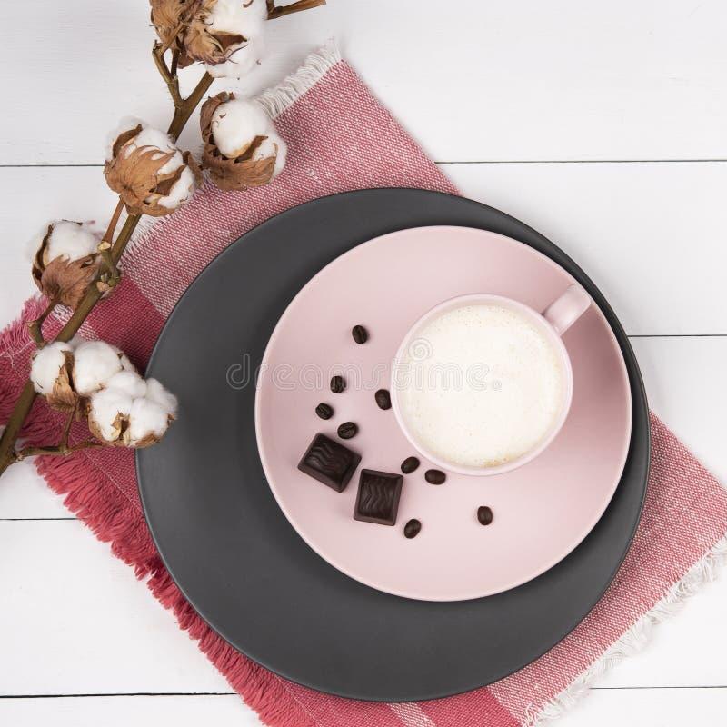 Kawowy latte na menchii, szarość pastelu talerzu z bawełnianej drewnianej tło koralowej pieluchy odgórnym widokiem i obraz royalty free