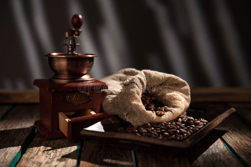 Kawowy młyn na ciemnym nieociosanym tle Drewno stół fotografia stock