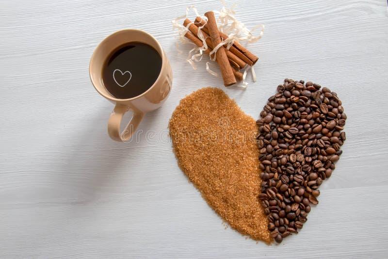Kawowy serce z brązu cukierem i kawą w filiżance, obrazy royalty free