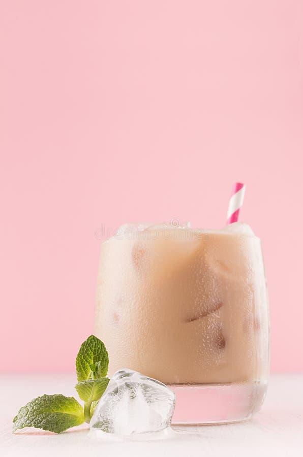 Kawowy zimny alkoholu koktajl w czara z kostka lodu, zieleni mennica, pasiasta słoma w pastelu świetle - różowy nowożytny restaur zdjęcia royalty free