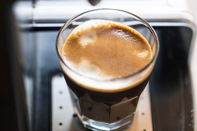 Kawy espresso dwoista filiżanka świeżo robić na kawowym maszynowym zbliżeniu z śmietankowym spienia, gorąca brązu aromata kawa zdjęcie royalty free