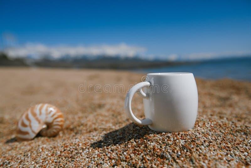 Kawy espresso filiżanka na issyk-kul plaży piasku z górami zdjęcia royalty free