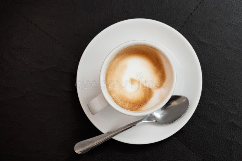 Kawy espresso macchiato w białej ceramicznej filiżance z spodeczka metalu łyżką odizolowywającą na czarnej skóry powierzchni z gó zdjęcie royalty free