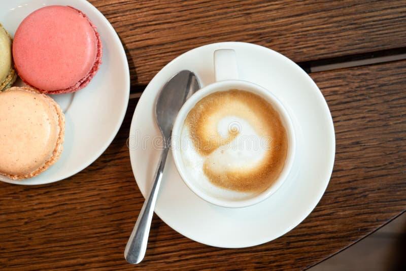 Kawy espresso macchiato w białej ceramicznej filiżance z spodeczkiem i spon obok talerza z macarons na brązu drewna powierzchni z obraz royalty free