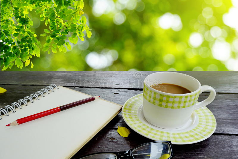 Kawy i notatnika strona z ołówkiem na drewnianym stole nad natury zieleni liśćmi fotografia royalty free