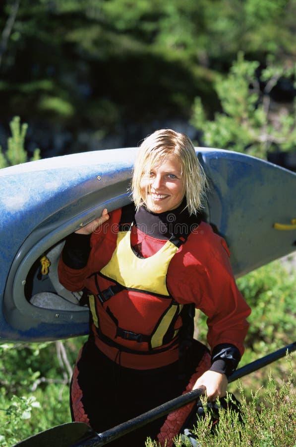 Kayak de transport de jeune femme image libre de droits