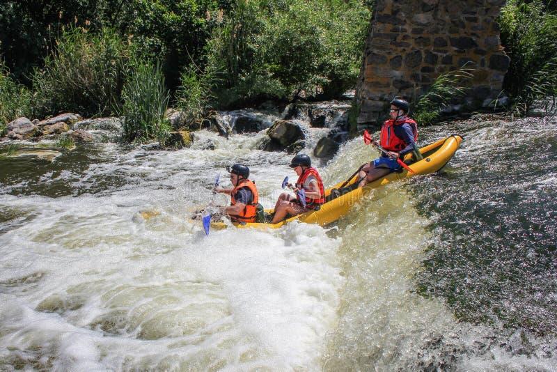 Kayak dell'acqua bianca di tre uomini sullo sport del fiume, di estremo e di divertimento ad attrazione turistica fotografia stock libera da diritti