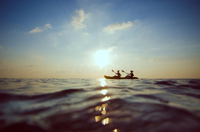 Kayak della gente al tramonto immagini stock libere da diritti