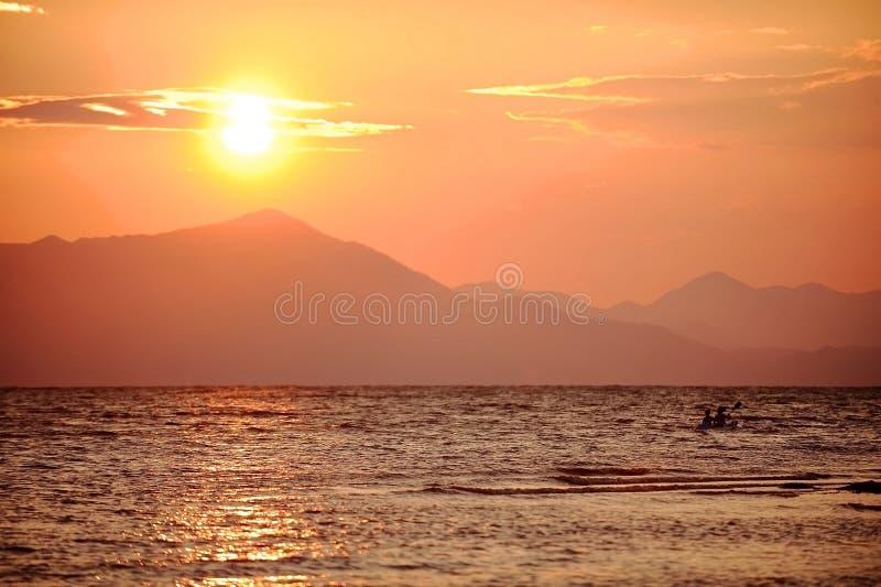 Kayak della gente sul lago Shkodra al tramonto fotografia stock libera da diritti