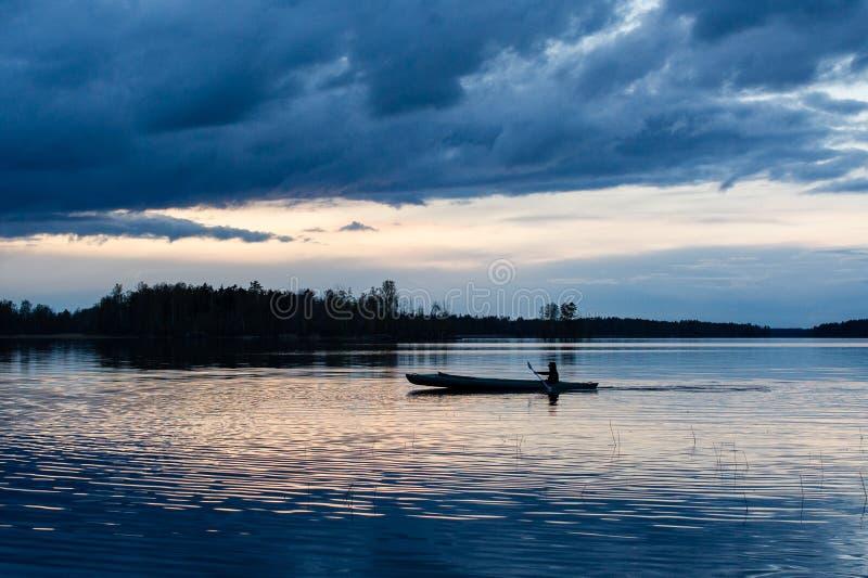 Kayak di tramonto nel lago fotografia stock libera da diritti