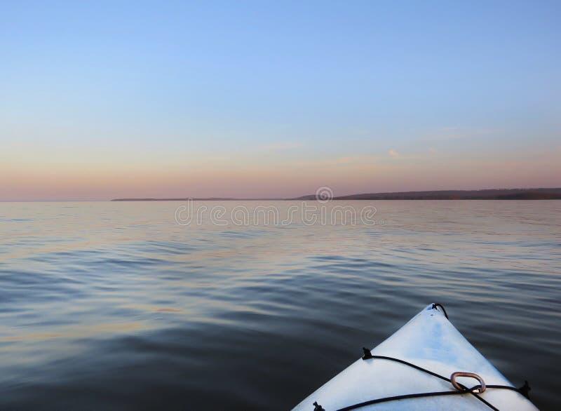 Kayak em um grande lago no alvorecer ou no crepúsculo imagem de stock royalty free